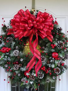 This 24 inch handcrafted wreath is bursting with red berries, pine cones with hand painted white tips, and a few small bright red apples. Atop the wreath rests a handmade red bow. The berries and bow are wired into place. Some of the pine cones are wired into place while others are Front Door Christmas Decorations, Christmas Front Doors, Pine Cone Decorations, Holiday Wreaths, Holiday Crafts, Holiday Decor, Christmas Pine Cones, Christmas Hanukkah, Outdoor Christmas