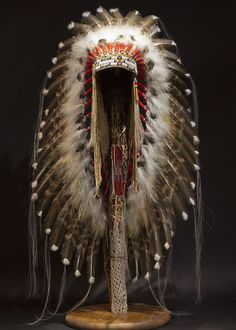 "This Victory Headdress is of a plains-style construction. Measuring in at over 36"" long, this piece is impressive in both size and craftsmanship. Each feather is carefully painted, and each bead is painstakingly stitched into a durable leather base to provide a lifetime of displayed beauty. Stand sold separately."