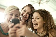 Young female friends looking at cellphone in cafe bar