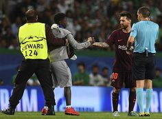A fan is removed by a steward from the pitch after hugging Barcelona's Argentinian forward Lionel Messi during the UEFA Champions League Group D football match Sporting CP vs FC Barcelona at the Jose Alvalade stadium in Lisbon on September 27, 2017. / AFP PHOTO / FRANCISCO LEONG