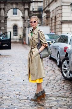 Street style from London Fashion Week. Model Laura Bailey covers up her colorful outfit with a classic trench. Wedge booties are ideal for cobblestone streets. Laura Bailey, London Fashion Weeks, Rainy Day Fashion, Winter Fashion, Vetements Clothing, Vanessa Jackman, London Look, Look At You, Mellow Yellow