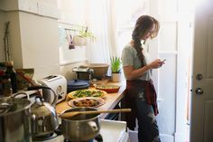 Woman cooking texting with cell phone in kitchen
