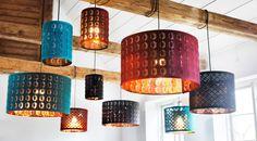 Forskellige lamper og lampeskærme hængt op i træbjælker i et lyst rum