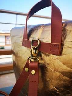 A shiny bronze paper-leather backpack with vegetable tanned leather straps and carry handle. This bag is handmade and has a weathered leathery look to it. Leather Bags, Leather Backpack, Vegetable Tanned Leather, Sustainable Fashion, Things To Come, Handle, Bronze, Backpacks, Paper