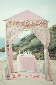 Pink and silver beach wedding ceremony canopy.