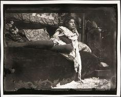 Model reclining on the couch in Mucha's studio, Rue du Val-de-Grâce, Paris. (1899)