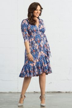 Add our plus size Flirty Flounce Wrap Dress to your closet with a funky pink peach and blue print. Shop our entire made in the USA collection online at www.kiyonna.com.