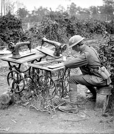 WWI, 21 July 1917, Fampoux ; Soldier of the 9th Division using two salvaged sewing machines as a writing desk. Cropped. ©IWM Q 5700