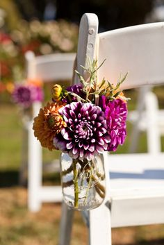 lovely isle runner flowers in purple and orange & after the ceremony use them on the food table. double duty. Just an idea if you are having seating available during the ceremony.