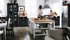 Mix & match IKEA kitchen styles! Back to back kitchen islands and a glass door cabinet in an open spaced kitchen.