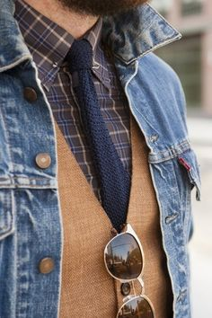 The wonderful mix of a plaid shirt, a simple tie, the rustic vest, and the rugged jean jacket is perfectly tied together by the very cool sunglasses. Perfect!