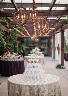 Under the terrace roof at Doris Duke Center- Get Lit twinkle lights and a trio of Gold Quatrefoil pendants. Watered Garden flowers. Party Tables linens. Gather Together planning. Katherine Miles Jones Photography.