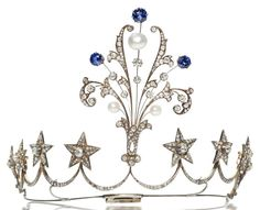 An antique diamond, pearl, and synthetic sapphire tiara, French, circa 1860, centering a knife-edge plume of old European, old mine and rose-cut diamonds, baroque pearls, and (later) synthetic sapphires, completed by a band of eight old European-cut diamond star-shaped clusters; with French assay marks; with original fitted case from Guillote, 20 Rue Thérèse, Paris, embossed with a crown and K.M. on the cover; estimated total diamond weight: 8.25 carats; mounted in silver topped gold.