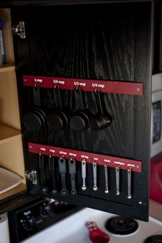 Such a smart idea!! Measuring cups and spoons inside your cabinet door. I live in a small apartment aka has a small kitchen so this is great. I am going to use the blog's tutorial, but instead of screwing the panels on, I am going to use removable 3M tabs since I rent. Then I can take them wherever I move next!