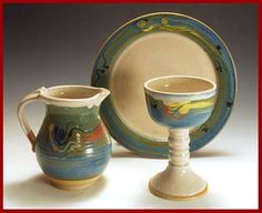 Old Farmhouse Pottery (farmpots.com) Communion Set.  Three-piece communion set of chalice, plate (paten), and pitcher. Ivory glaze with sea green, turquoise, and yellow slip glazes. The plate is 10 1/2 inches in diameter.