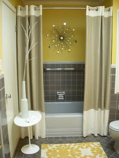 Using two shower curtains instead on one completely changes the way the bathroom looks!    I love the colors here! Typically not a fan of yellow but this looks great!