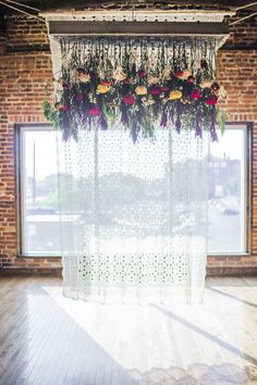 ceremony backdrop with hanging flowers, photo by Hannah Elaine Photography http://ruffledblog.com/the-2nd-notwedding-nashville #weddingceremony #backdrops