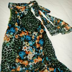 Beautiful green cheetah/floral top Sleeveless, green cheetah, blue roses and multiple flowers.  Ties with sash on left shoulder, which has ruffles at end of sash .  Also has ruffles at bottom of top. Perfect for skinny jeans or leggins!  Lined with a sheer thin green liner. Runway Paris Tops Blouses