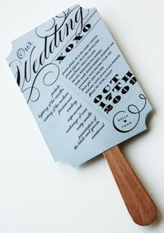 print programs on tag board, glue craft sticks to back: viola! program doubles as fan for guests!