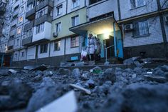 People walk out of a building near damaged pavement following a shelling, according to locals, in Donetsk February 4, 2015. REUTERS/Maxim Shemetov