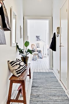 Hallway, white floor, white walls, wooden bench, aztec pillow and rug.