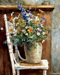 Art by Stella Bruwer earthen ware urn with midsummer flowers on shabby white chair with caning seat by wooden cupboard