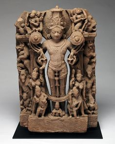 """Central India; c. 12th century The Sun God standing with customary lotuses, surrounded by consorts, deities, and mythical animals. Custom base.This is a substantial and high quality piece, worthy of serious attention. Dimensions: 27"""" (69cm) high, excluding base."""