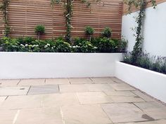 hardwood privacy screen trellis slatted fence with raised beds patio paving small garden clapham london (1)