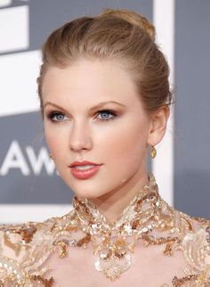 Taylor Swift's Beauty Transformation - 2012: Taylor Swift balances her high-necked dress with a high bun at the annual Grammy awards.