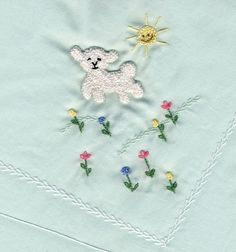 French knot lamb, chain stitch sun, assorted stitches for flowers, green & white featherstitch. Worked on pale green Swiss flannel blanket.  Made by Trudy Horne.