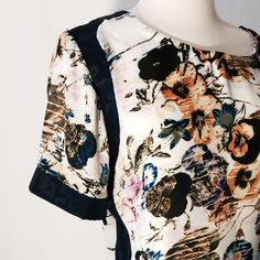 """Just In  Awesome Navy & White Silk Print Top Great print with navy, orange, yellow, blue and green flowers on a white background. This goop neck short sleeve blouse is Treme with navy accents along the shoulders hymns and science. This blouse has exposed back zipper closure and bust darts.   100% silk  Dry Clean  44"""" bust 26"""" overall length Tops Blouses"""