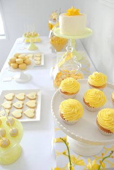 Beautiful dessert table. Yellow-themed tea party with lemon curd cupcakes, macarons, cookies and cake.