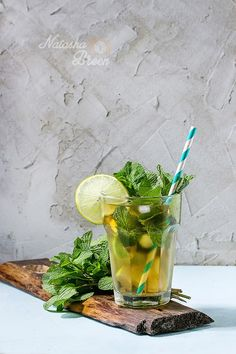 Sunny Ice Tea - Glass of Iced green tea with lime, lemon, mint and ice cubes on wooden chopping board over light blue textured background.