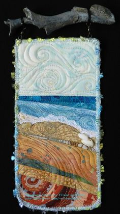 Southern Shores.  A small art quilt by Eileen Willliams, hanging from found shell fragment.