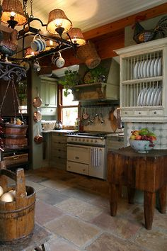 Painted cabinets, antique looking stove, huge plate rack, warm colors, pot hanger with ceramic ware and baskets and wine barrel veggie holder.  Love this warm welcoming kitchen.