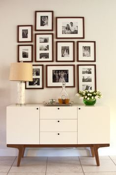 Family photos in blk & wh, modern display, great mid-century storage piece, mother-of-pearl lamp. AT KELLY DESIGN - interior design #atkellydesign