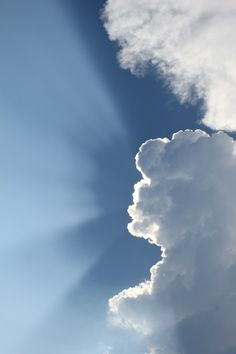 Sun Shining Behind Clouds in Blue Sky  Free Stock Photo