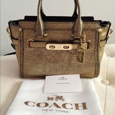"✨SALE✨ Auth Coach Gold Metallic Pebble Swagger Bag So gorgeous & trendy 100% Authentic Coach Mini carryall / gold metallic leather with statement belting and bold double-turnlock hardware, two interior pockets, zip-top closure, and detachable & adjustable shoulder strap. Comes with its dustbag!  -Brand new condition. No signs of wear.   -Approx. Measurements:  Length – 7.25""/ Height – 5.75""/ Width – 4"" / Handle drop – 3"" / Shoulder strap drop - 23""   ❁ Send me your best offer! I accept ALL…"
