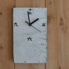 Horologe murale, en céramique raku, avec les nombres en idéogrammes japonais, blanc et noir