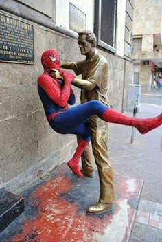 Spider Man having fun with statues.