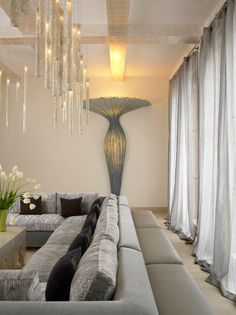 Icicle chandelier above grey sectional. Winter decor.