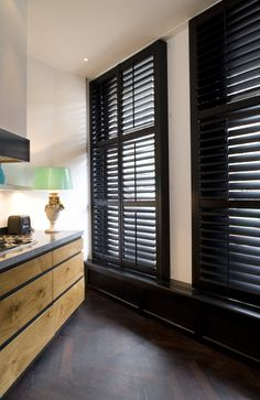 Zwarte shutters complementeren de houten keuken. Met shutters creëer je in de keuken een bijzondere sfeer. Het gebruik van zwarte shutters dragen bij aan de stoere look in deze keuken.
