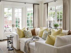 """The designer chose a Mitchell Gold sectional for the family room and filled it with pretty pillows. """"The homeowner wanted a piece she and her son and husband could really use and cuddle up in,"""" says Jessica. """"It can be changed around because it's so versatile. Her son has even had sleepovers on it."""""""