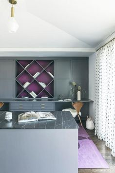 Gray built-in cabinets with brass hardware flank a built in bookcase accented with a purple back and fixed above a soapstone countertop finishing a built in desk seating two Cherner Chairs placed on a purple rug. Purple Home Offices, Purple Office, Home Office Colors, Grey Office, Home Office Decor, Office Ideas, Office Color Schemes, Blue Color Schemes, Bedroom Color Schemes