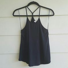 ZARA W&B collection tank Black tank with skinny racer back straps. Flowy fit. Scoop neck. Almost a muscle cut but not as deep. It's a great basic. Washed and worn 2 times and in great condition. I cut the long tag as its quite annoying so I'm not sure on the exact fabric. But it's super soft! I'm going to say a rayon cotton blend. Zara Tops Tank Tops