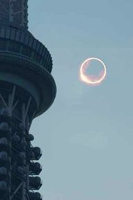 An annular eclipse is seen beside the Tokyo Sky Tree tower in Tokyo's Sumida Ward at 7:34 a.m.