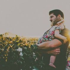 "He insists upon carrying our sleepy baby girl (so aptly named ""Ruby"") in a field of sunflowers--you know, all that stuff."