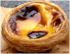 One of the most iconic treats in Portugal is the Pastel de Nata. A custard tart similar to a cream brulee in a phyllo shell. Delicious with cinnamon and powdered sugar. Portugese Custard Tarts, Portuguese Tarts, Portuguese Desserts, Portuguese Recipes, Köstliche Desserts, Delicious Desserts, Custard Desserts, Alcoholic Desserts, Strawberry Desserts