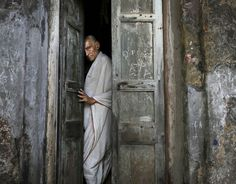 A man closes the door to his home in an alleyway near the Kali Temple in the eastern Indian city of Kolkata, April 14.