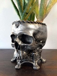 Life sized sculpture of a hollow human skull set into an ornate base. 10 tall and cast in resin, hand painted.